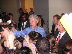 Bill Clinton reaches for something to sign