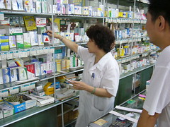 Chinese pharmacy technician grabbing medicine ...