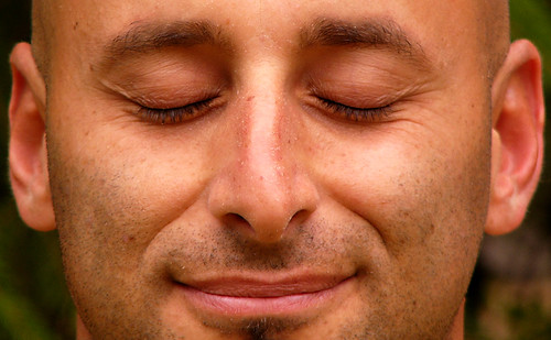 Primer plano de un hombre con los ojos cerrados, meditando