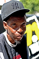 Charleston Blue (Shavar Ross) Tags: california summer people ny man face sadness losangeles eyes sad faces homeless august2005 poor highcontrast cap hollywood africanamerican hungry hollywoodblvd blackman yankees hobo needy hardtimes recession homelesspeople shavarrosscom