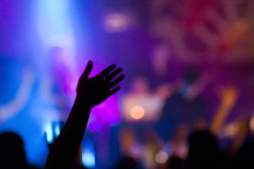 Fotografía de una mano derecha alzada entre la oscuridad de una sala de conciertos con las luces del escenario al fondo