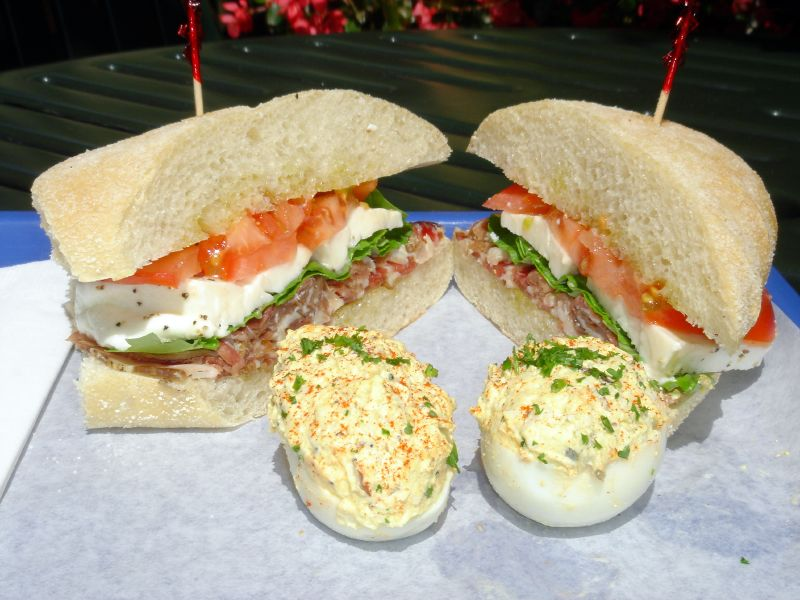 Prosciutto di parma sandwich with fresh mozzarella, fresh basil and fresh tomatoes and stuffed eggs