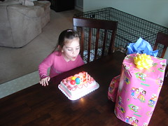 Belle blowing out the candles on her cheesy last minute cake