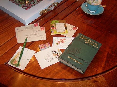 vintage stationary, stacks of old stamps, an antique pen and a Louisa May Alcott treasure