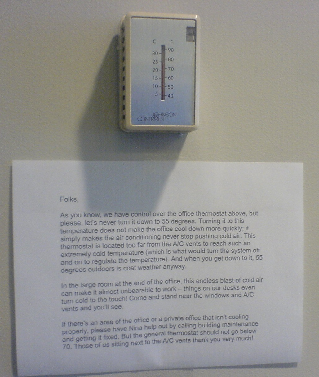 Folks, as you know, we have control over the office thermostat above, but please, let's never turn it down to 55 degrees. Turning it to this temperature does not make the office cool down more quickly; it simply makes the air conditioning never stop pushing cold air. This thermostat is located too far from the A/C to reach such an extremely cold temperature (which is what would turn the system off and on to regulate the temperature). And when you get down to it, 55 degrees outdoors is coat weather anyway. In the large room at the end of the office, this endless blast of cold air can make it almost unbearable to work — things on our desks even turn cold to the touch! Come and stand near the windows and the A/C vents and you'll see. If there's an area of the office or a private office that isn't cooling properly, please have Nina help out by calling building maintenance and getting it fixed. But the general thermostat should not go below 70. Those of us sitting next to the A/C vents thank you very much!