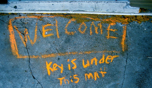 "Graffiti on floor outside door which reads ""Welcome key is under mat"""