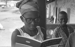 Girl next door pretending to read, Kabala, Sierra Leone (West Africa), 1968 (gbaku) Tags: pictures africa girls west girl scarf children photo necklace 60s child photos head african headscarf picture sierra photographs sierraleone photograph heads westafrica afrika 1960s anthropologie leone sixties anthropology africain afrique ethnography ethnology africaine  kabala westafrican headcloth warawara ethnologie classicblackwhite afrikas