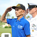 World War II veteran and a Sailor salute a wreath during a ceremony in commemoration of the 69th ann