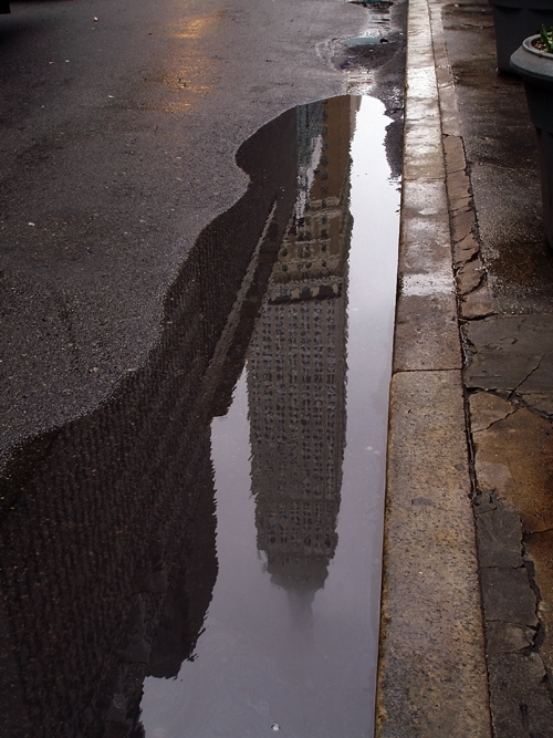 reflection of Empire State Building in puddle