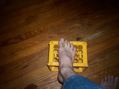 Luca's foot resting on a yellow plastic basket.