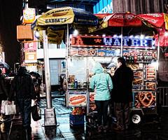 DSC07988b (nick_scotcher) Tags: hotdogstand kiosk seller pretzel timessquare raining umbrella couple reflection street rain