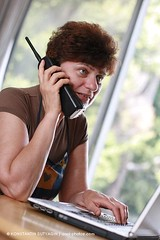 "Mature woman at home talking on the phone with hand on laptop. Think ""home office"" for example. (Konstantin Sutyagin) Tags: light portrait people woman home vertical female computer shopping notebook happy person one office day technology hand phone adult laptop internet tube mother talk social headset apron communication indoors mature single casual 50s brunette activity talking cordless housewife antenna active caucasian strobist"