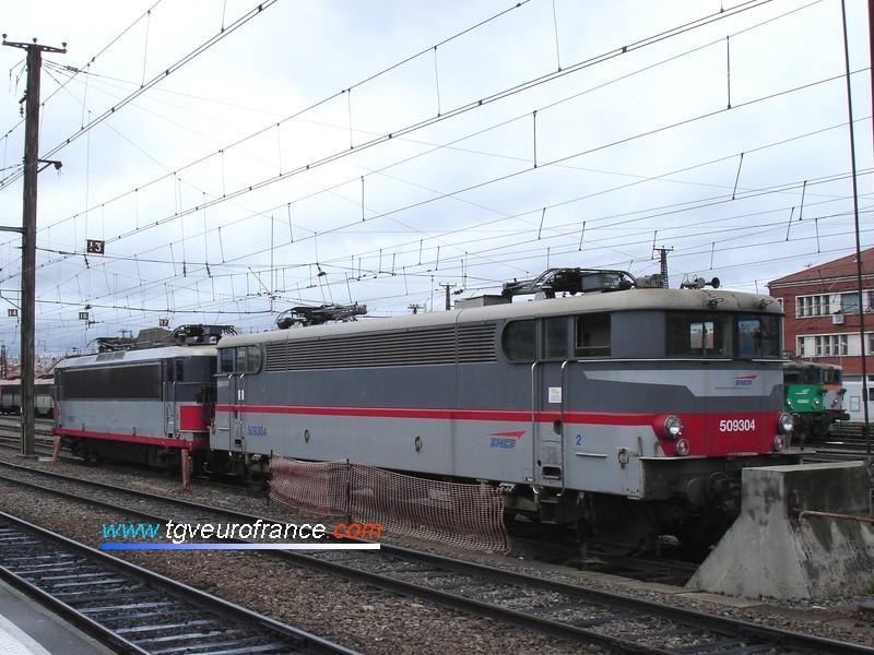 Deux locomotives électriques monotension en livrée Multiservice stationnent au dépôt SNCF de Toulouse.