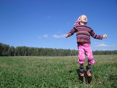 Young girl jumping on top of a grassy hill