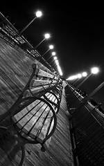 Everyone suffers in silence a burden (navid j) Tags: sf sanfrancisco california blackandwhite bw white black night bench angle perspective embarcadero pier7