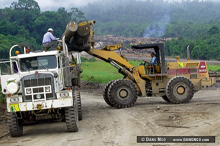 A log grappler of the Rimbunan Hijau Timber company loads logs onto a logging truck in the Baram District of Sarawak, Malaysia. In the background is one of this international timber company's log sort