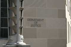 close up of the side of the u.s. department of justice building, gray bricks and the letters spelling out 'department of justice'