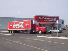 A large Coca-Cola truck with a refrigerated trailer... (Steve Brandon) Tags: ontario canada shop retail truck logo geotagged photo store parkinglot magasin ottawa coke pharmacy camion suburb cocacola apothecary nepean brand development pharmacie stripmall chemists deliverytruck shoppersdrugmart stationnement   easypix merivaleroad merivalerd ruemerivale cheminmerivale