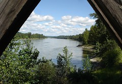 View through foot bridge over Fraser River (peggyhr) Tags: wood blue trees sky white canada clouds river shadows britishcolumbia shore fraser bushes beams gravel quesnel thebigone travelerphotos cloudsandanythingelse allaboutwater