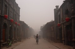 Cyclist on Nan Da Jie (NowJustNic) Tags: china street people bike fog person smog construction nikon cyclist edited scooter coolpix lantern  moped shanxi pingyao   flickrelite coolpixe4200