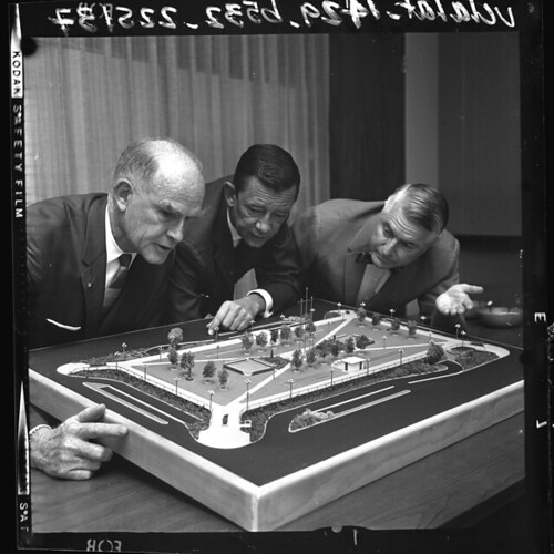 William Frederickson Jr., Robert Howe and William T. Wright examining model of planned redesign of Pershing Square, Calif., 1964