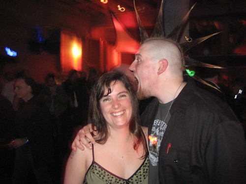 man with a big mohawk gnawing on a woman's head