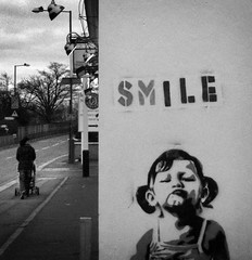 smile (medejavecu) Tags: road street uk greatbritain bridge england bw baby white streetart black cute london girl smile square blackwhite stencil pub europe grafitti child carriage grain mother banksy kind squareformat boardwalk suburb root buggy mutter weiss schwarz hounslow mdchen kinderwagen pram periphery krnung lchle