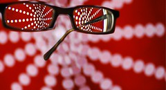 an abstract dot pattern is blurry in the back ground, a pair of eyeglasses is in the foreground, the abstract dot pattern is clear behind the lenses