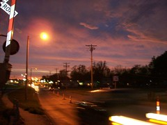Underneath the Pawnee Sky (andre seward) Tags: road street railroad pink blue trees sunset orange white signs black blur trafficlights lines car sign yellow clouds speed train circle concrete lights spring construction crossing purple traffic telephone headlights walmart pole sidewalk wires gloss asphalt past parallel coolest telephonewires 7up cones rotate pawnee magneta braums 7upsign telphonepoles