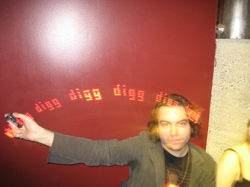 Philip Torrone waving an LED stick that makes the word DIGG in the air