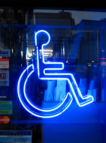 A wheelchair symbol lit up in florescent light