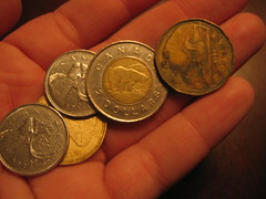 A hand holding Canadian loonies, quarters, and a toonie