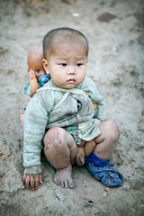 muddy boy with a doll on his back (phitar) Tags: boy thailand kid doll dusk refugee interestingness1 2006 topf300 topf200 laotian phetchabun phitar hmon