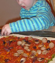 awesomeGrrl putting toppings on her pizza