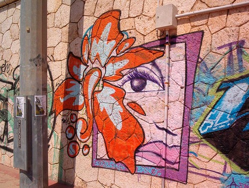 graffiti of bright big orange orchid over a woman's face