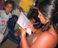 A women drafts an idea on Dotmocracy sheet while her children watch.