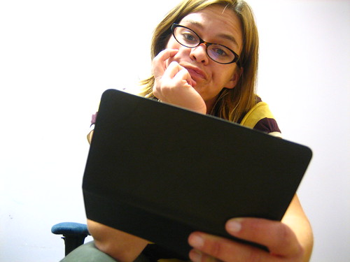 A woman looking at her checkbook with a resigned expression