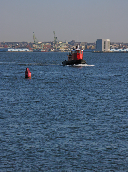 small red tugboat on the Hudson River, NYC