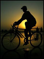 the cycle boy (ali khurshid) Tags: pakistan boy sunset beach silhouette solitude time calm cycle alikhurshid clifton changinglight