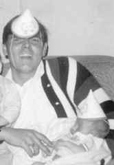 Dad holding newborn me at my sister's first birthday party