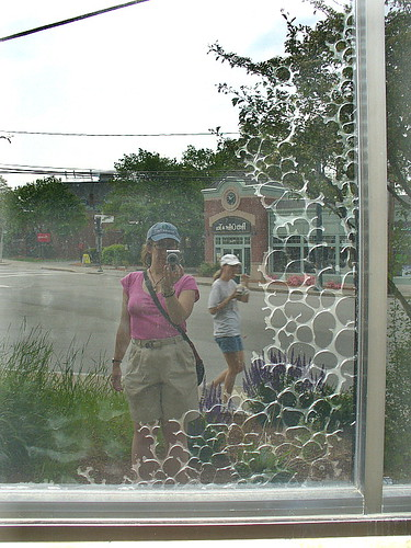 Reflection with ice-cream eating passerby