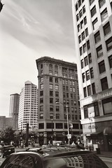 Downtown in black and white (Elena777) Tags: seattle street city blackandwhite bw reflection building film car architecture 35mm buildings downtown kodak scan scanned 4thave kodakdisposablebwcamera