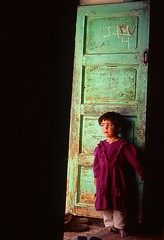 they can't see me here... (janchan) Tags: door portrait people afghanistan verde green kids children war asia village purple bambini retrato documentary guerra velvia porte coolest ritratto reportage ghazni blackribbonicon thetaleofaurezu whitetaraproductions sfidephotoamatori