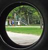 Looking through the round window (KiwiNessie) Tags: newzealand people girl playground topv111 horizontal digital children outdoors unfound flickrchallenge themed tyres nzl unedited mc05negativespace fcm003
