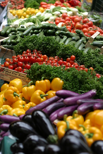Photograph of vegetables in large baskets at a farmers market, including eggplant, bell peppers, tomatoes, summer squash, and bok choy. Image taken by computix and licensed under Creative Commons.