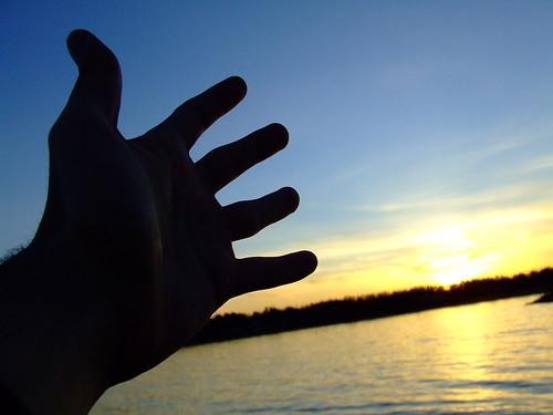 Fotografía de la silueta de una mano con el mar al fondo en una puesta de Sol
