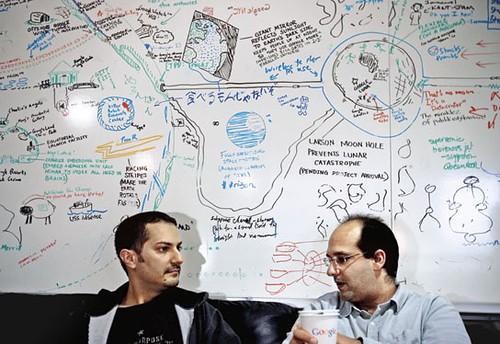 Dua orang karyawan Google sedang berbincang-bincang sambil minum kopi di depan idea board, sebuah papan tulis tempat menuliskan ide-ide. Dari sinilah ide-ide besar Google lahir.