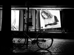 """Your Partner in Beauty"" (helmet13) Tags: street bw woman berlin beauty bicycle promotion germany poster nightshot shopwindow nocturne windowshopping aoi 100faves peaceaward heartaward world100f leicaxvario"