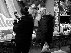 nocturnal market 010 (byronv2) Tags: edinburgh edinburghbynight edimbourg scotland blackandwhite blackwhite bw monochrome peoplewatching candid street night nuit nacht princesstreet princesstreetgardens market stall kiosk festivemarket game ball woman asian cellphone phone mobilephone playing