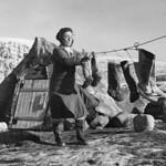 """Inuit woman """"Aasivak Evic"""" hangs kamiits (sealskin boots) to dry, Pangnirtuuq (Pangnirtung), Nunavut / Aasivak Evic, une femme inuite, suspend des kamiit (bottes en peau de phoque) pour les faire sécher, à Pangnirtuuq (Pangnirtung), au Nunavut thumbnail"""